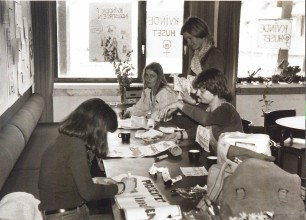 """At the then existing women's house, feminist are painting banners. On the windows it says """"Women's house"""" and """"Women in the industry"""". Students at RUC were very much socially engaged with problems in society, writing research-projects to understand and deal with these. For example the problems and welfare of women workers in factories, which constituted a large part of the labour force at that time."""